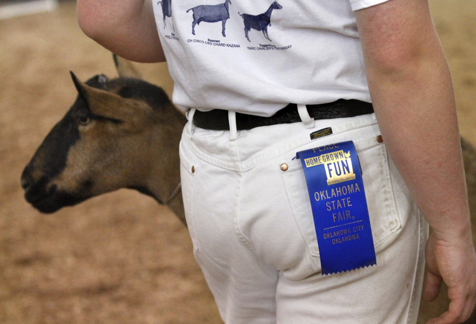 A first place blue ribbon,  awarded to a previous goat, dangles from the pocket of this teen's jeans as he shows another gloat, hoping to win more blue ribbons at the Oklahoma State Fair on Wednesday, Sep. 19, 2012.  Photo by Jim Beckel, The Oklahoman.