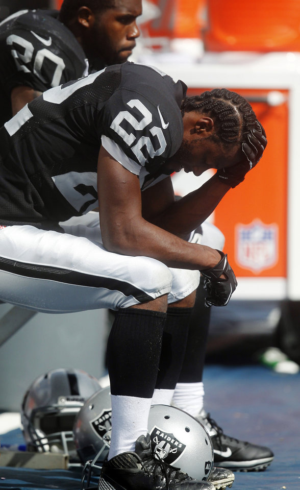 Photo -   Oakland Raiders running back Taiwan Jones (22) bows his head on the sidelines during the second half of an NFL football game against the Miami Dolphins, Sunday, Sept. 16, 2012, in Miami. At top left is running back Darren McFadden. The Dolphins won 35-13. (AP Photo/Wilfredo Lee)