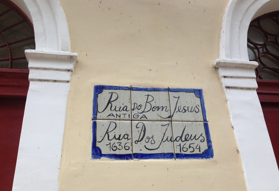 Photo - In this June 24, 2014 photo, a street sign for Rua do Bom Jesus decorates the side of a Jewish memorial and cultural center in Recife, Brazil. The building sits upon the ruins of what is widely accepted to have been the first synagogue built in the Americas. Recife was initially settled by the Portuguese in the 1530s, but the Dutch invaded in 1630 and ruled the region for 24 years. It was during this period that Jews who had previous settled in Amsterdam, many of them of Portuguese descent, began moving to Recife for business and religious purposes. (AP Photo/Brett Martel)