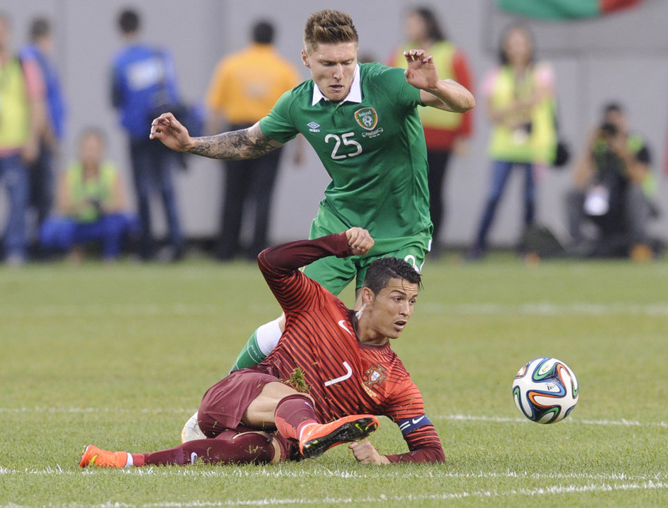 Photo - Portugal's Cristiano Ronaldo passes the ball as Republic of Ireland's Jeff Hendrick (25) defends during the first half of an international friendly soccer match Tuesday, June 10, 2014, in East Rutherford, N.J. (AP Photo/Bill Kostroun)
