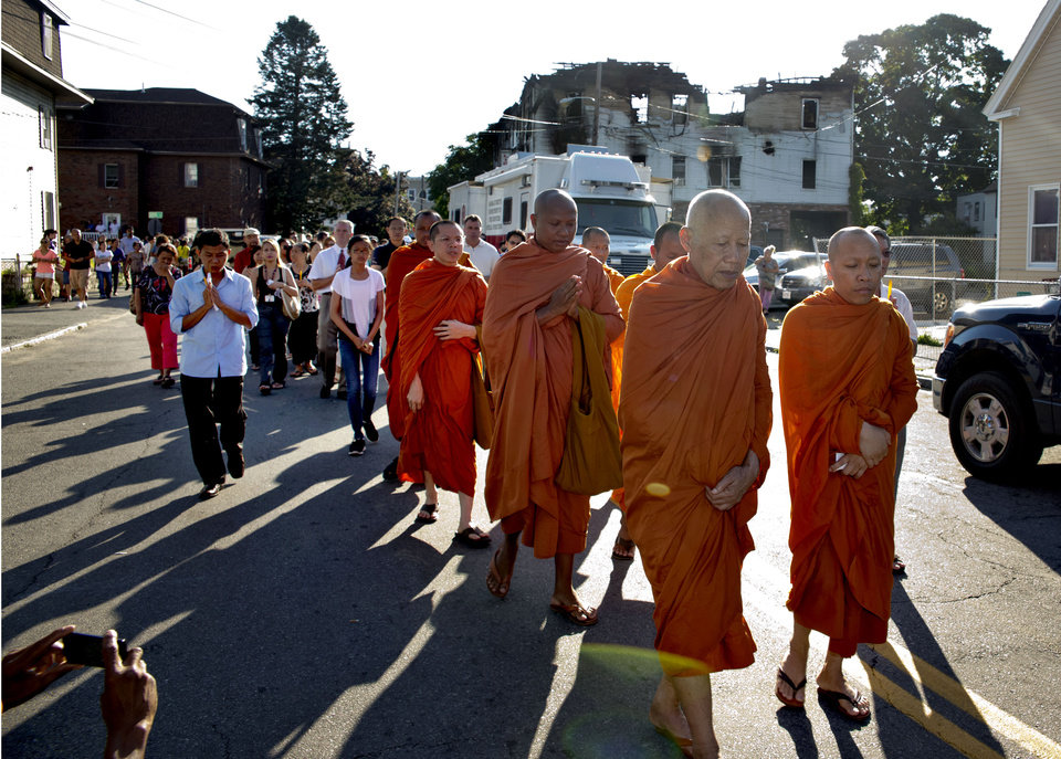Photo - Buddhist Monks from Glory Buddhist Temple lead people from the community away from a burned-out apartment building that  killed 7 people Thursday July 10,  2014 in Lowell, Mass. (AP Photo/The Boston Globe, Matthew J. Lee)  MANDATORY CREDIT. NO ONLINE USE. MAGS OUT. NO SALES. BOSTON OUT. QUINCY OUT.