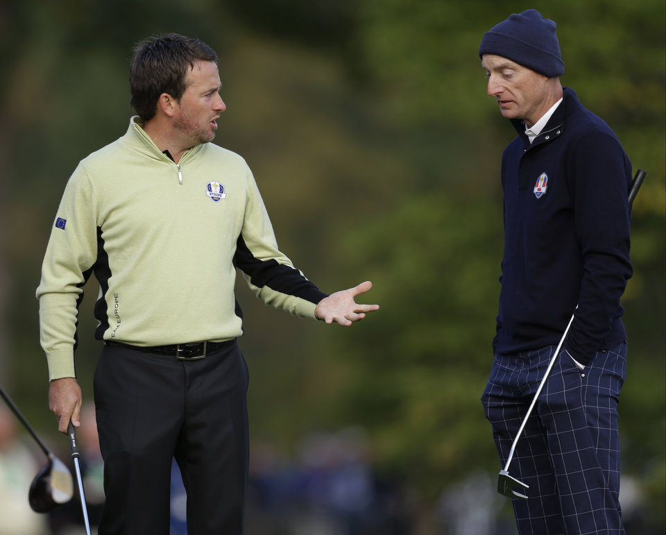 Photo -   Europe's Graeme McDowell, left, and USA's Jim Furyk talk about getting relief during a foursomes match at the Ryder Cup PGA golf tournament Friday, Sept. 28, 2012, at the Medinah Country Club in Medinah, Ill. (AP Photo/David J. Phillip)