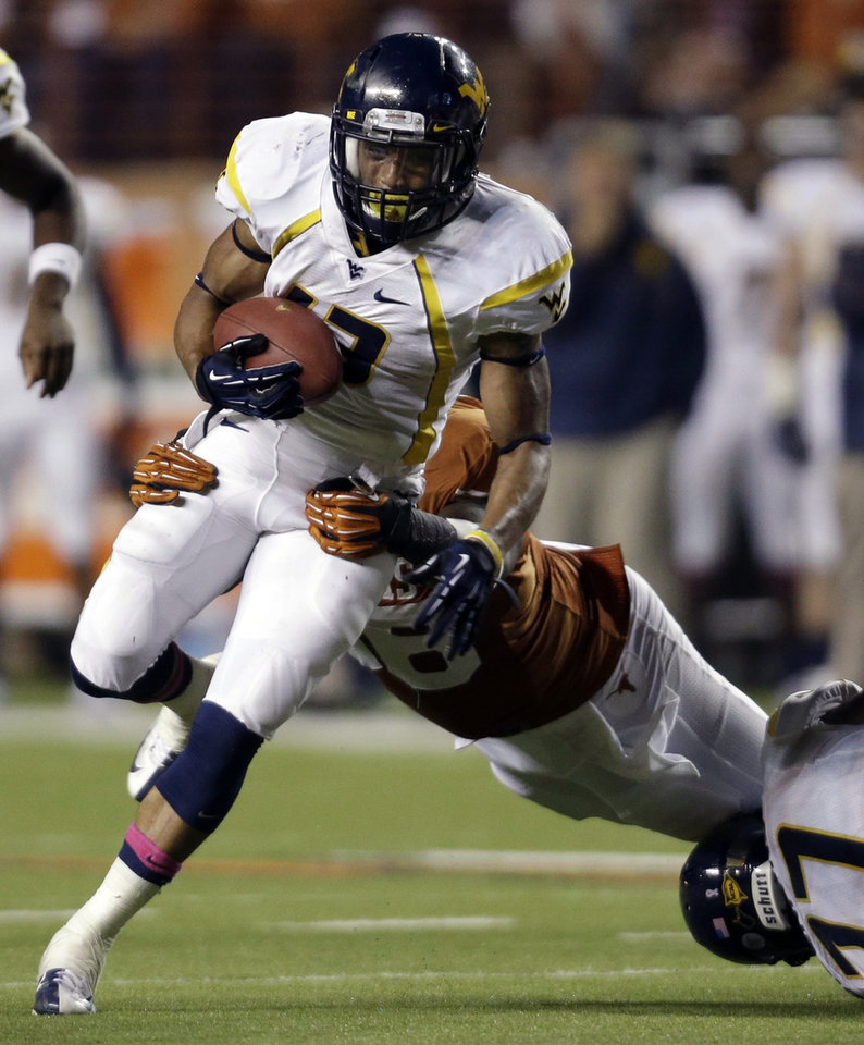West Virginia's Andrew Buie, left, is brough down by Texas defender Chris Whaley, center, during the second quarter of an NCAA college football game on Saturday, Oct. 6, 2012, in Austin, Texas. (AP Photo/Eric Gay)