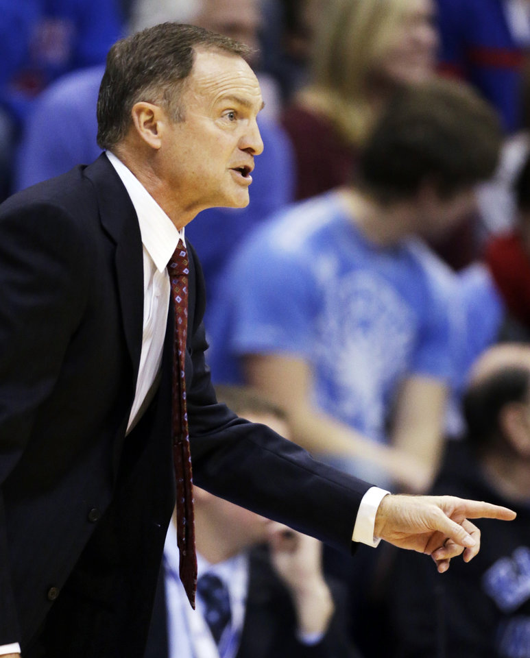 Photo - Oklahoma head coach Lon Kruger directs his team during the first half of an NCAA college basketball game against Kansas in Lawrence, Kan., Saturday, Jan. 26, 2013. (AP Photo/Orlin Wagner)