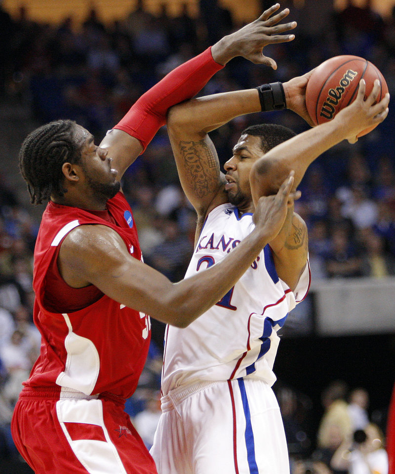 Photo - Jeff Pelage (32), left, of Boston defends Markieff Morris (21) of Kansas in the second half during the NCAA men's basketball tournament second round game between Boston and Kansas at the BOK Center in Tulsa, Okla., Friday, March 18, 2011. Kansas won, 72-53. Photo by Nate Billings, The Oklahoman