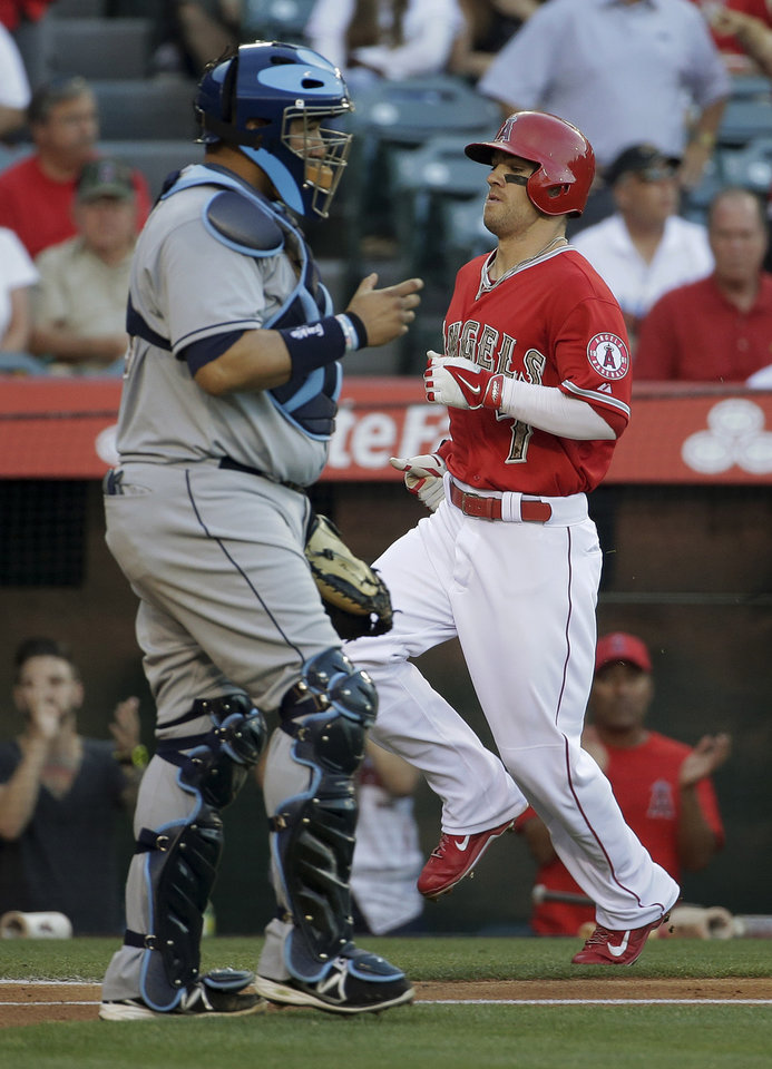 Photo - Los Angeles Angels' Collin Cowgill, right, scores past Tampa Bay Rays catcher Jose Molina on a single by Howie Kendrick during the first inning of a baseball game in Anaheim, Calif., Saturday, May 17, 2014. (AP Photo/Chris Carlson)