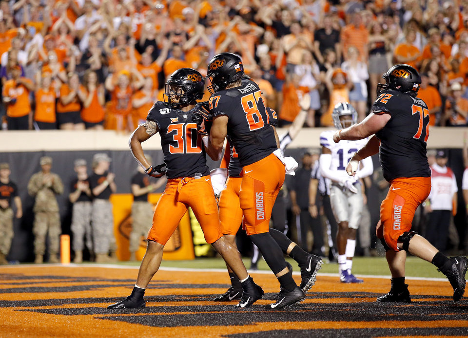 Photo - Oklahoma State's Chuba Hubbard (30) celebrates with Logan Carter (87) and Johnny Wilson (72) in the fourth quarter during the college football game between the Oklahoma State Cowboys and the Kansas State Wildcats at Boone Pickens Stadium in Stillwater, Okla., Saturday, Sept. 28, 2019.  The play was called back because of penalties. OSU won 26-13. [Sarah Phipps/The Oklahoman]