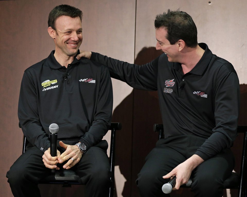 Photo - Kyle Busch, right, jokes with new teammate Matt Kenseth, left, during a news conference at Joe Gibbs Racing in Huntersville, N.C., Thursday, Jan. 24, 2013, as part of the NASCAR Sprint Cup Media Tour. (AP Photo/Chuck Burton)