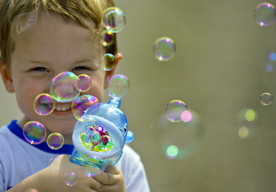 Photo - James McGlathery, 3, of Del City has a big smile as he watches the bubbles made from his bubble machine during the 2013 Oklahoma State Fair on Monday, Sep. 16, 2013. Photo by Chris Landsberger, The Oklahoman