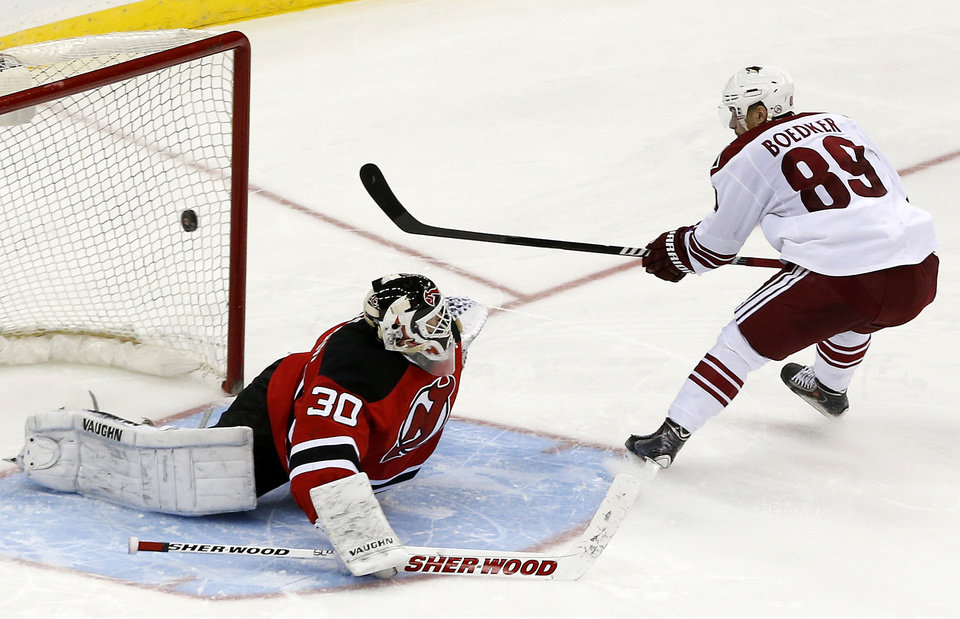 Photo - Phoenix Coyotes left wing Mikkel Boedker (89), of Denmark, scores a goal on New Jersey Devils goalie Martin Brodeur during a shootout in an NHL hockey game, Thursday, March 27, 2014, in Newark, N.J. The Coyotes won 3-2. (AP Photo/Julio Cortez)