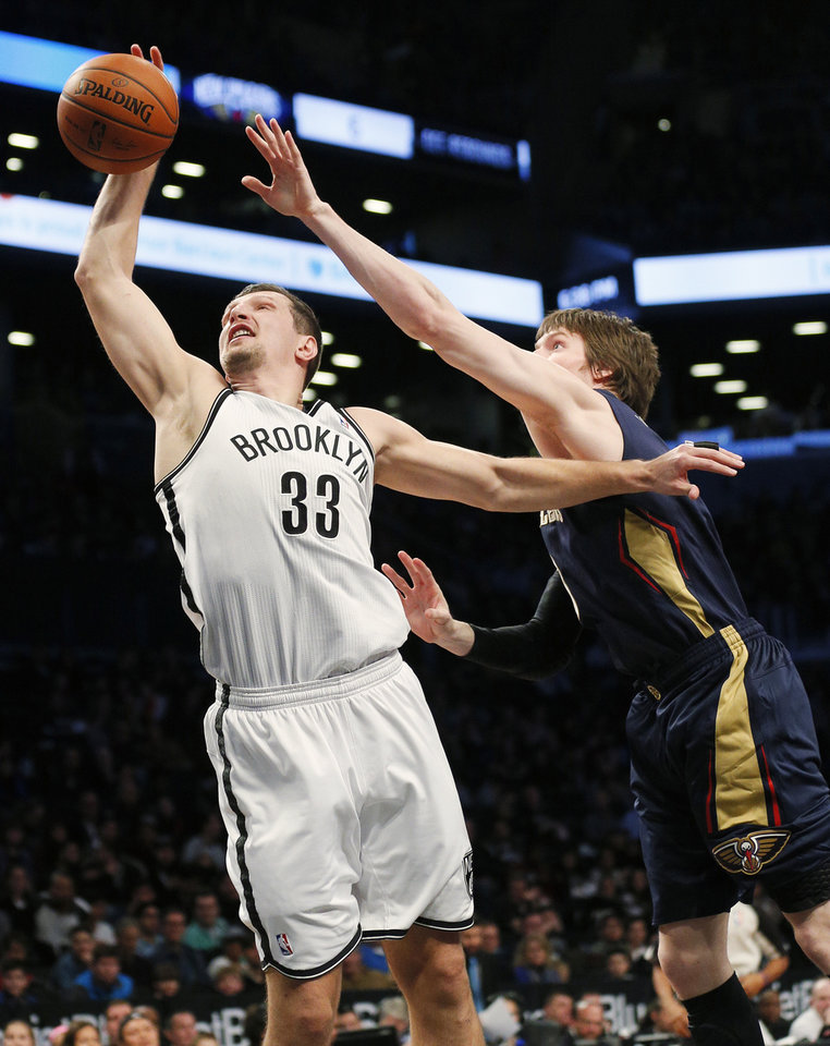 Photo - Brooklyn Nets forward Mirza Teletovic (33) pulls in a rebound in front of New Orleans Pelicans forward Luke Babbitt in the first half of an NBA basketball game on Sunday, Feb. 9, 2014, in New York. (AP Photo/Paul J. Bereswill)