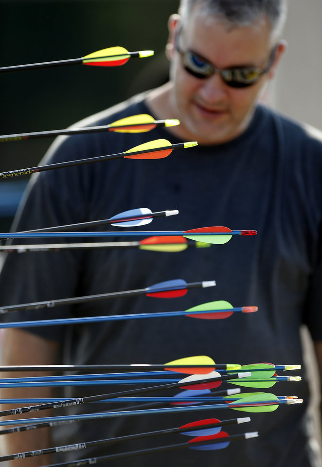Photo - Brian Carter takes out his arrows and his son's, Riley, 9, after shooting at a target during a Junior Olympic Archery Development Club shoot put on by the Trosper Archery Club on Saturday, August 24, 2013, at Trosper Park in Oklahoma City. The two have been attending the Saturday shoots all summer and was one of over 60 participants, from beginners to intermediates, that took part in the shoot which takes place every Saturday. For $5 each person is supplied with equipment and instruction starting at 9am for beginners and 10am for intermediate shooters. Photo by Bryan Terry, The Oklahoman