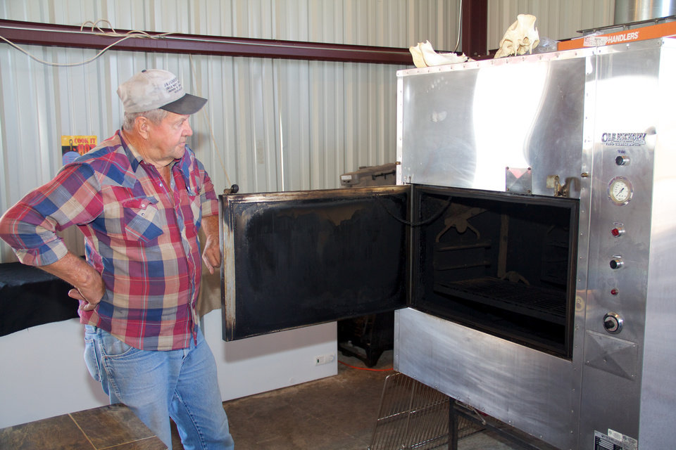 Photo - Wayne Brinkley prepares the smoker at Erick-based Somekinda Catering, which provides food to oilfield workers throughout western Oklahoma and the Texas panhandle.  photo by Adam Wilmoth