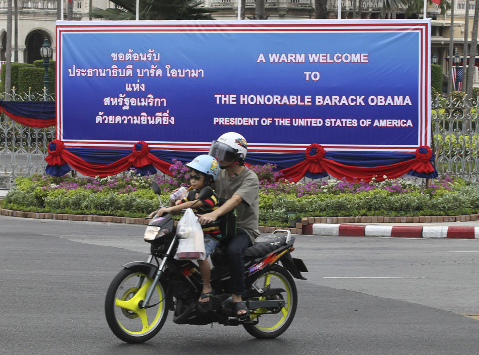 Photo -   A man rides on a motorbike with a child past a welcoming banner for U.S. President Barack Obama erected outside the government house in Bangkok, Thailand Saturday, Nov. 17, 2012. Obama will arrive in Thailand on Sunday, Nov. 18, 2012 as part of his southeast Asian nations tour which includes Myanmar and Cambodia. (AP Photo/Apichart Weerawong)