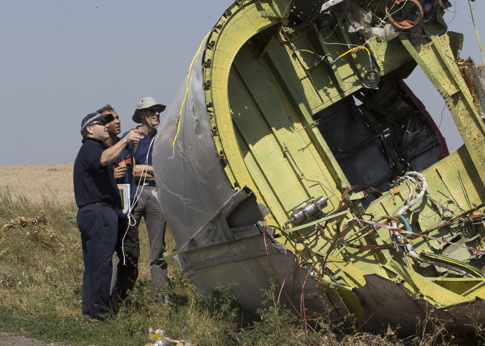 Photo - Australian and Dutch experts examine a piece of the Malaysia Airlines Flight 17 plane, near the village of Hrabove, Donetsk region, eastern Ukraine Friday, Aug.1, 2014.  The investigators from the Netherlands and Australia plus officials with the Organization for Security and Cooperation in Europe traveled from the rebel-held city of Donetsk in 15 cars and a bus to the crash site outside the village of Hrabove. Then they started setting up a base to work from at a chicken farm. The investigative team's top priority is to recover human remains that have been rotting in midsummer heat of 90 degrees (32 degrees Celsius) since the plane went down on July 17. (AP Photo/Dmitry Lovetsky)