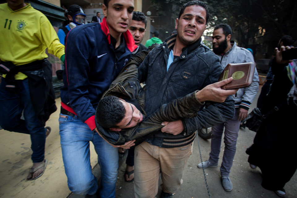Photo - A protester wounded in clashes with security forces is evacuated from the site in the Mohandiseen district of Cairo, Egypt, Saturday, Jan. 25, 2014. In large, state-backed rallies complete with dancing horses and traditional music, military supporters celebrated the anniversary of Egypt's 2011 uprising Saturday, calling for the army chief to run for president. At the same time, security forces cracked down on rival demonstrations by Islamist supporters of the ousted president — and by secular activists critical of both camps.(AP Photo/Eman Helal)