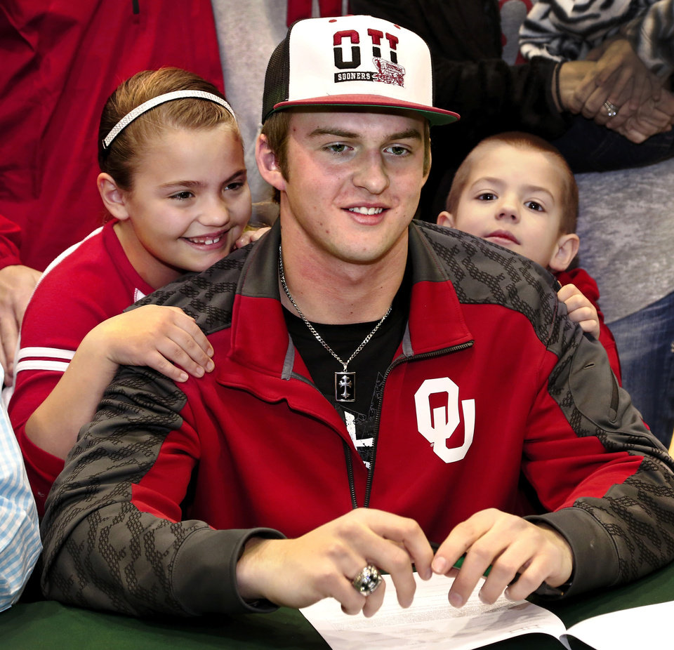 Photo - Justice Hansen, center, is an Edmond Santa Fe quarterback who signed a letter of intent to play football with OU during signing day ceremony in the gymnasium at Edmond Santa Fe High School on Wednesday, Feb. 5, 2014.  Siblings Kasia, 8, left, and Acyn, 6, were beside Hansen when he signed the ceremonial letter.   Photo by Jim Beckel, The Oklahoman