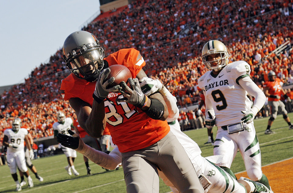Photo - OSU's Justin Blackmon (81) makes a touchdown catch in the second quarter despite the defense of Baylor's K.J. Morton (8) near Chance Casey (9) during a college football game between the Oklahoma State University Cowboys (OSU) and the Baylor University Bears (BU) at Boone Pickens Stadium in Stillwater, Okla., Saturday, Oct. 29, 2011. Photo by Nate Billings, The Oklahoman
