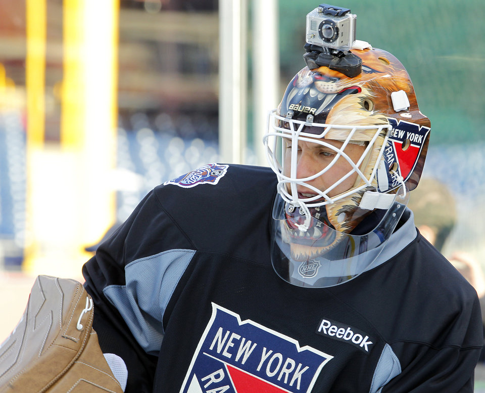 Photo - FILE - In this Sunday Jan. 1, 2012 file photo, New York Rangers' goalie Martin Biron, sporting a helmet camera, warms up during practice for the Winter Classic hockey game, in Philadelphia. For adventure athletes, it's the new essential: a video of their exploits. Now only video action will do for a shoot-it-and-share-it generation of skiers and skydivers, snowboarders and bike riders. (AP Photo/Tom Mihalek, File)