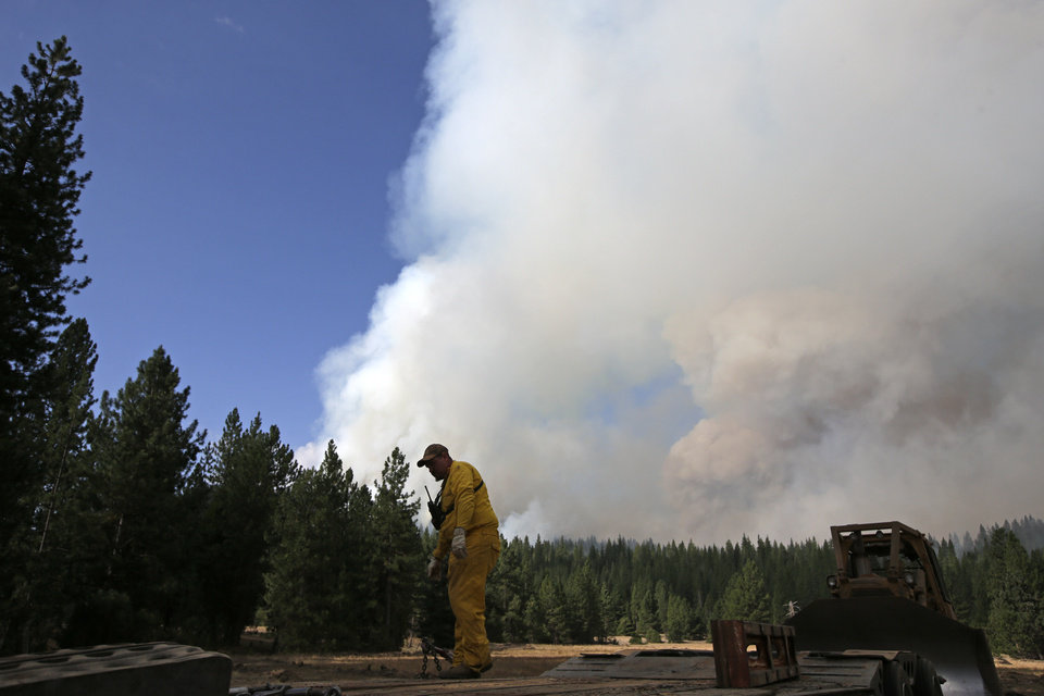Photo - A contractor prepares to load a bulldozer onto a trailer as a smoke plume from the Rim Fire rises near Yosemite National Park, Calif., on Sunday, Aug. 25, 2013. With winds gusting and flames jumping from treetop to treetop, hundreds of firefighters have been deployed to protect this and other communities in the path of the Rim Fire raging north of Yosemite National Park. (AP Photo/Jae C. Hong)