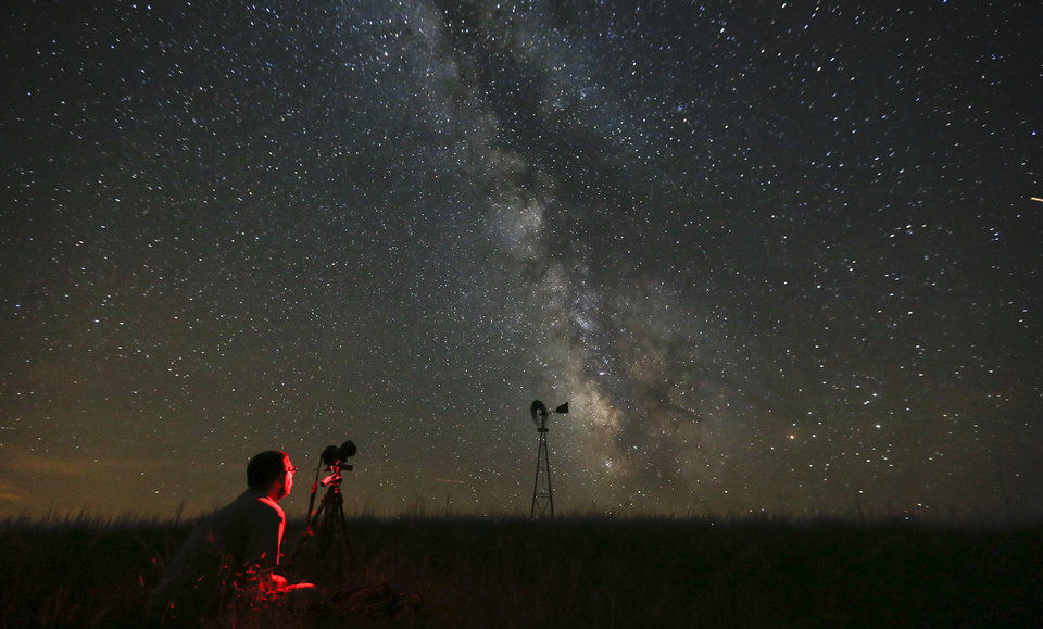 Photo - AP10ThingsToSee - Omaha photographer Lane Hickenbottom photographs the night sky in a pasture near Callaway, Neb., Wednesday, July 23, 2014. The Milky Way was visible to the naked eye. (AP Photo/The Wichita Eagle, Travis Heying)