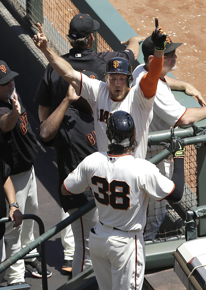Photo - San Francisco Giants' Hunter Pence, center, celebrates after hitting a two-run home run off of Atlanta Braves pitcher Julio Teheran with Michael Morse (38) during the first inning of a baseball game in San Francisco, Wednesday, May 14, 2014. (AP Photo)
