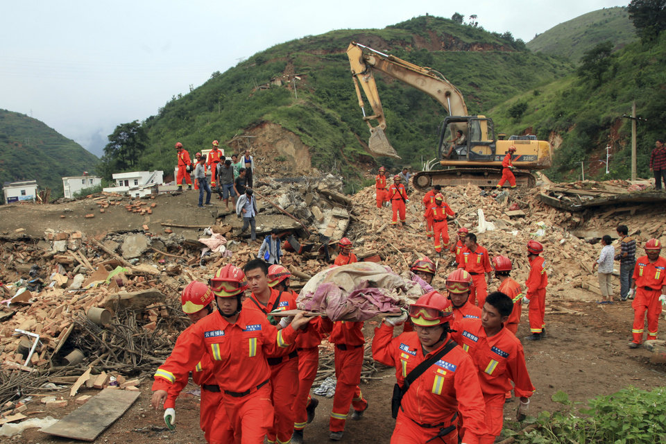 Photo - Rescue workers remove a dead body from the remains of a collapsed building at the epicenter of an earthquake that struck the town of Longtoushan in Ludian county in southwest China's Yunnan province Monday, Aug. 4, 2014.  Rescuers dug through shattered homes Monday looking for survivors of a strong earthquake in southern China's Yunnan province that toppled thousands of homes on Sunday, killing hundreds and injuring more than a thousand people. (AP Photo) CHINA OUT