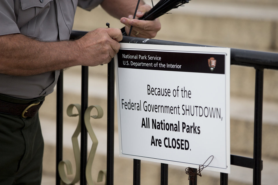 Photo - A National Park Service employee posts a sign reading