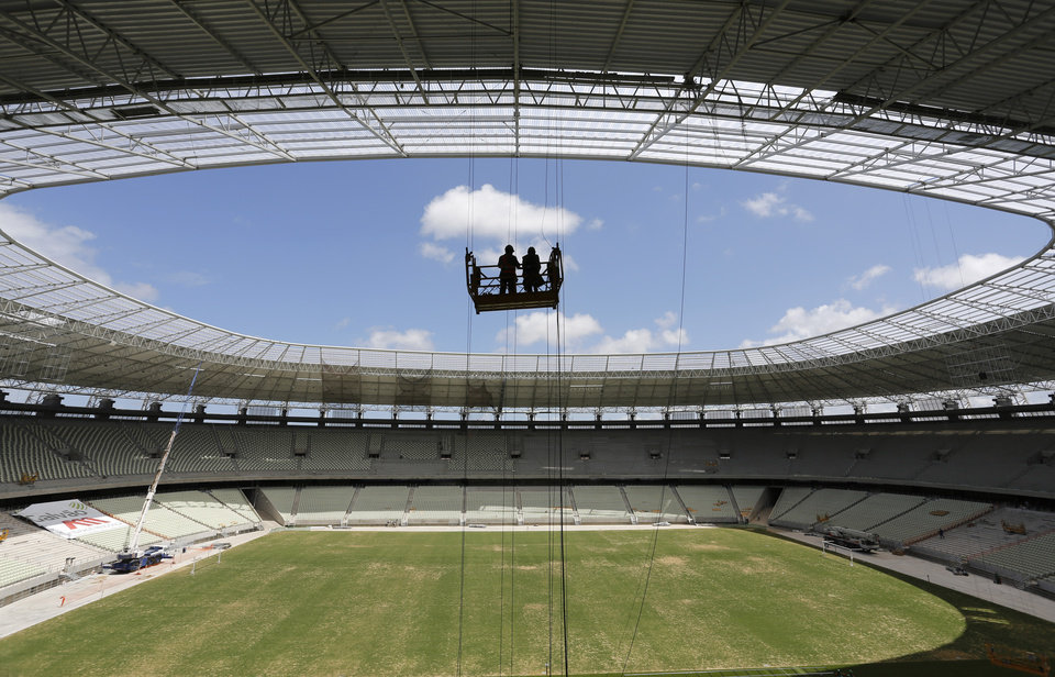 FILE - This Dec. 7, 2012 file photo shows workers silhouetted against the sky over the Estadio Governador Placido Castelo in Fortaleza, Brazil, Fortaleza will host matches of the 2014 soccer World Cup. (AP Photo/Ferdinand Ostrop, File)