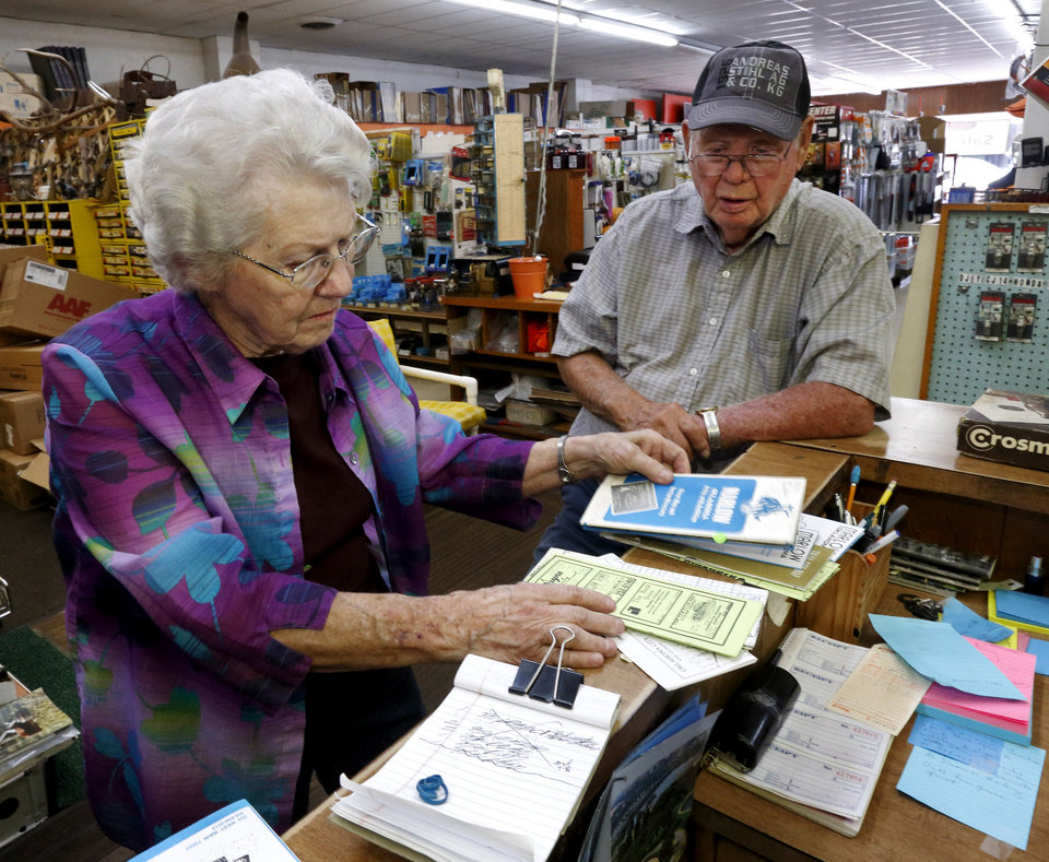 Photo - E.J. and Nancy Crow look at mementos in their OTASCO store on Tuesday, July 8, 2014 in Marlow, Okla.  Today their son Mike Crow runs the operation and retired son Ron helps out.  Photo by Steve Sisney, The Oklahoman