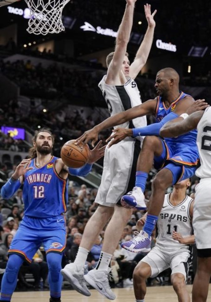 Photo -  Oklahoma City Thunder guard Chris Paul, right, passes to center Steven Adams (12) as he is defended by San Antonio's Jakob Poeltl during Thursday's game at AT&T Center. [AP Photo/Darren Abate]