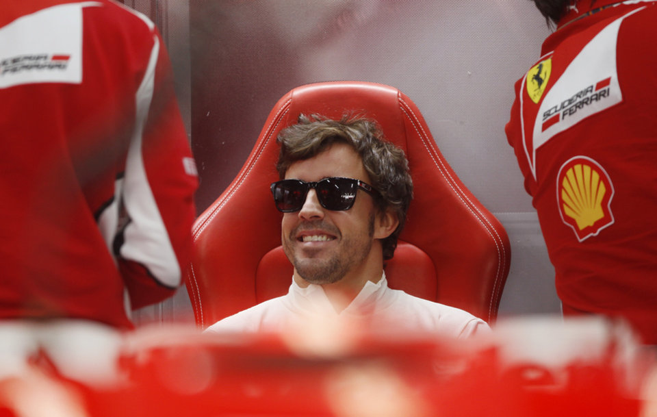 Photo -   Ferrari driver Fernando Alonso of Spain waits in the back of his pit lane garage during the first practice session for the Korean Formula One Grand Prix at the Korean International Circuit in Yeongam, South Korea, Friday, Oct. 12, 2012. (AP Photo/Dita Alangkara)