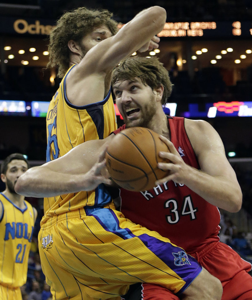Toronto center Aaron Gray (34) goes to the basket despite the defense of New Orleans center Robin Lopez (15) during the second quarter of an NBA basketball game at the New Orleans Arena in New Orleans, Friday, Dec. 28, 2012. (AP Photo/Dave Martin)