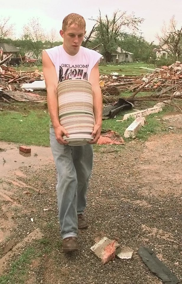 MAY 3, 1999 TORNADO: Tornado damage. Bryan Boley carries surviving plates out of the Mulhall School cafeteria.
