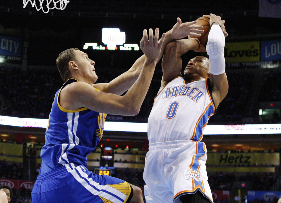 Oklahoma City Thunder guard Russell Westbrook (0) shoots as Golden State Warriors center Andris Biedrins, left, defends, in the first quarter of an NBA basketball game in Oklahoma City, Sunday, Nov. 18, 2012. (AP Photo/Sue Ogrocki)