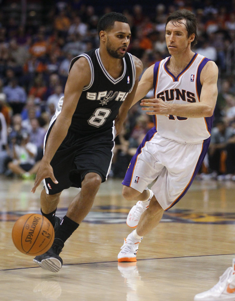Photo -   San Antonio Spurs' Patty Mills (8), of Australia, drives against Phoenix Suns' Steve Nash (13) during the first half of an NBA basketball game Wednesday, April 25, 2012, in Phoenix. (AP Photo/Matt York)