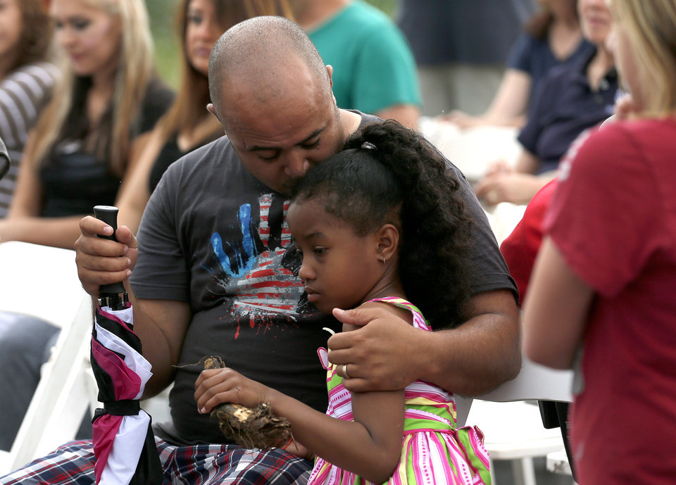 Photo - Anthony Alexander of Moore hugs his daughter, Viviana, 7, after she honored her dog Bobo at a memorial service Saturday at the Orr Family Farm, 14400 S Western, for animals who died in recent tornadoes.   SARAH PHIPPS - SARAH PHIPPS