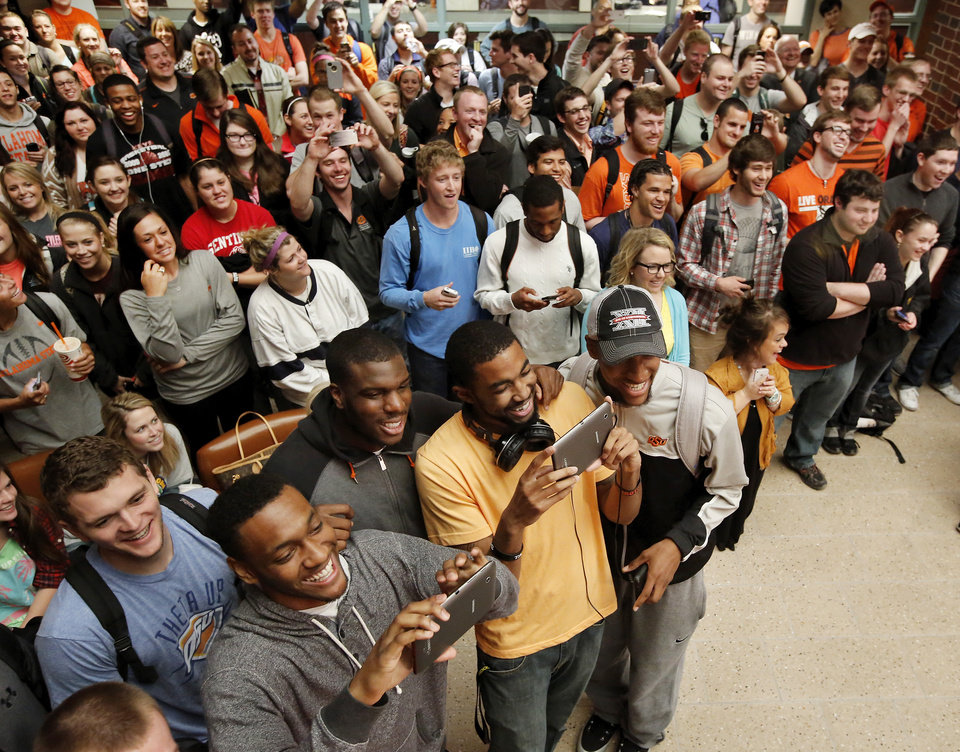 Students cheer and players take pictures as teammates are called to the stage. OSU basketball players Le'Bryan Nash, Markel Brown and Marcus Smart delighted  fans when they announced at a noontime press conference they intend to return for another season as members of the Cowboys basketball team. Cheering fans lined all levels in the Student Union atrium Wednesday, April 17, 2013.    by Jim Beckel, The Oklahoman.