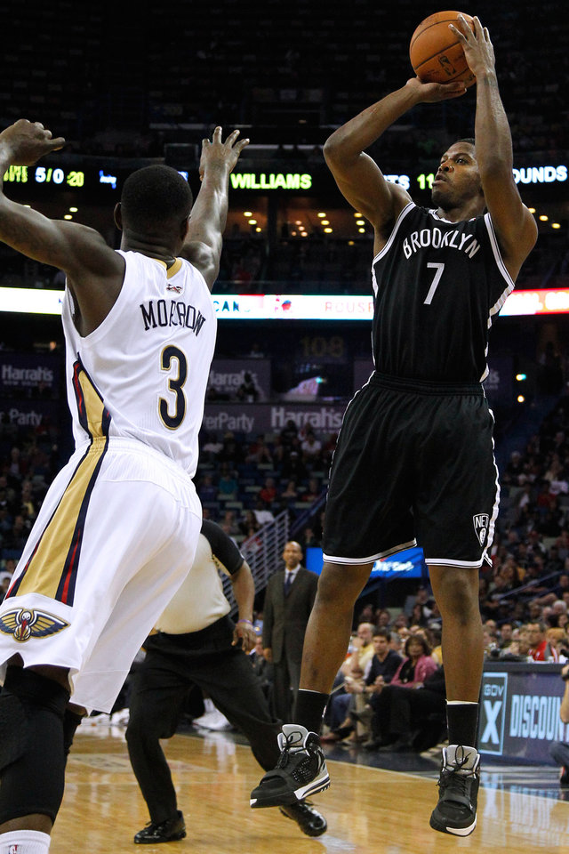 Photo - Brooklyn Nets guard Joe Johnson (7) shoots the ball over New Orleans Pelicans guard Anthony Morrow (3) during the first half of an NBA basketball game in New Orleans, Monday, March 24, 2014. (AP Photo/Jonathan Bachman)