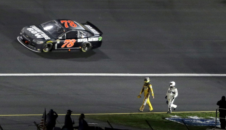 Photo - A safety crew worker chases Kyle Busch along the speedway apron after Busch crashed in Turn 3 during the NASCAR Sprint All-Star auto race, as Martin Truex Jr. (78) drives by at Charlotte Motor Speedway in Concord, N.C., Saturday, May 17, 2014. (AP Photo/Gerry Broome)