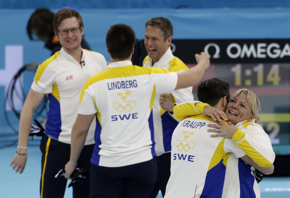Photo - Sweden's Sebastian Kraup hugs coach Eva Lund, far right, while celebrating their victory over China in the men's curling bronze medal game at the 2014 Winter Olympics, Friday, Feb. 21, 2014, in Sochi, Russia. (AP Photo/Robert F. Bukaty)