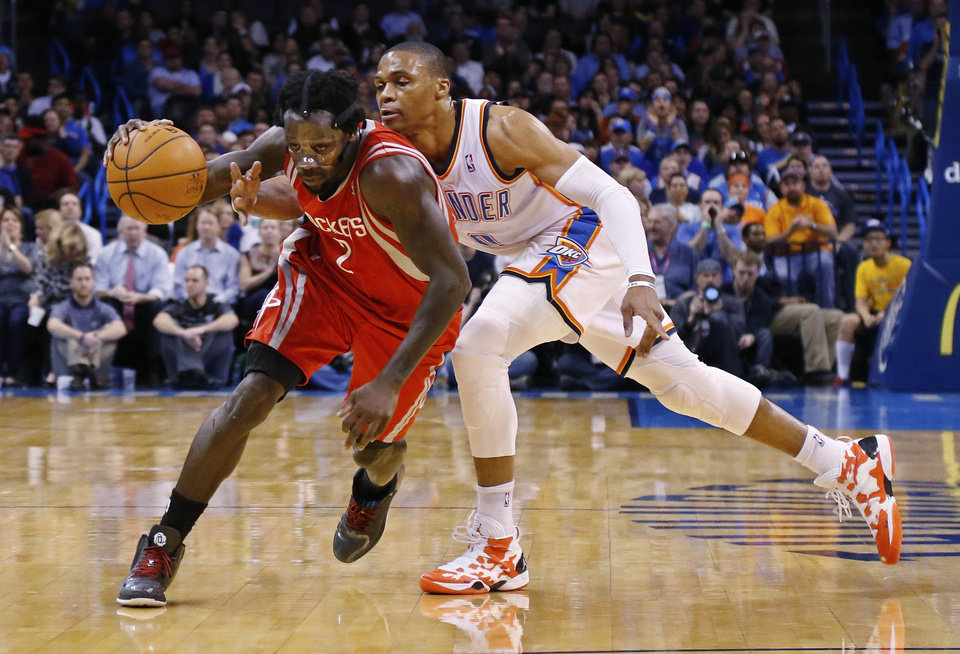 Houston Rockets guard Pat Beverley (2) drives around Oklahoma City Thunder guard Russell Westbrook (0) during the first quarter of an NBA basketball game in Oklahoma City, Tuesday, March 11, 2014. (AP Photo/Sue Ogrocki)