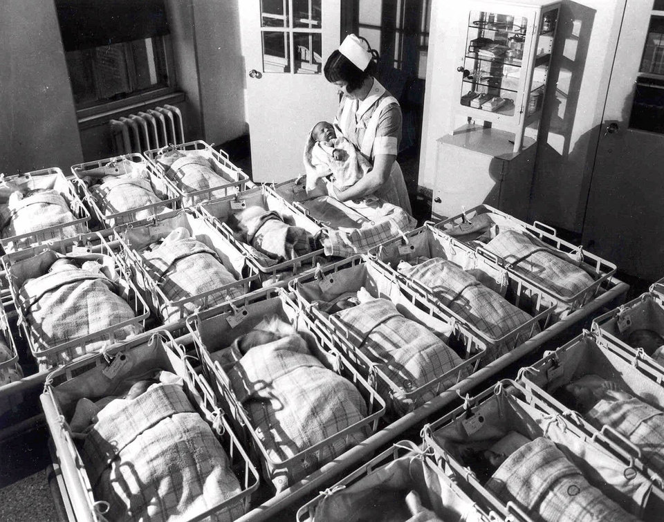 Photo - FILE - In this 1930 file photo, a nurse holds a baby in the nursery of the Pennsylvania Hospital in Philadelphia. Five years after the deepest global recession since the 1930s sent birth rates plunging around the world, many couples are still not having children. That's good news if you're worried about an overcrowded planet. But it's bad for the economy.  (AP Photo/File)