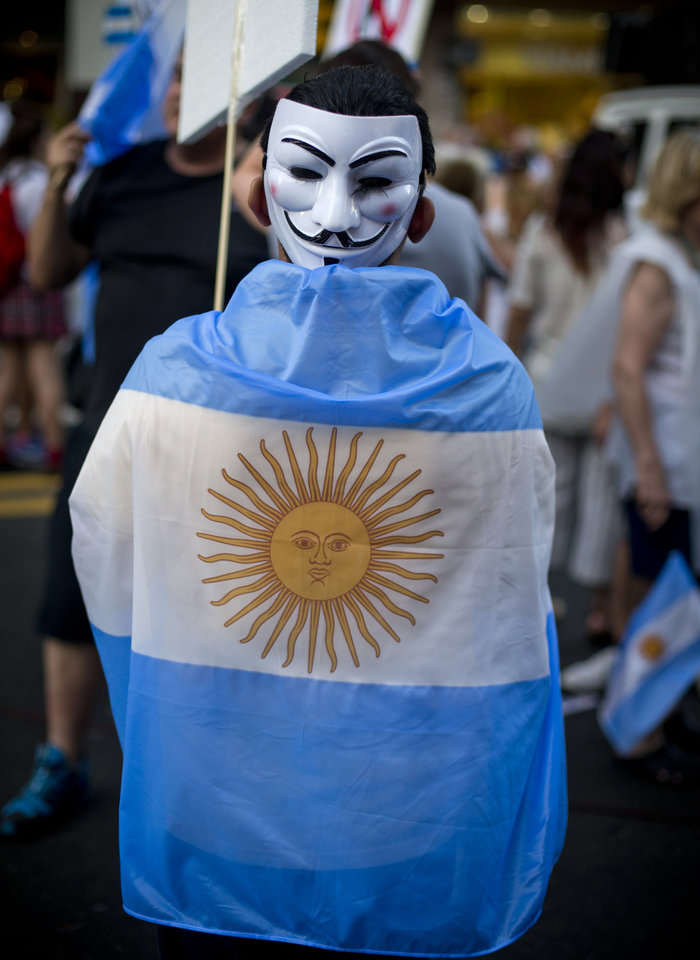 Photo -   A protester wearing a mask on the back of his head and an Argentine flag marches during anti government demonstration in Buenos Aires, Argentina, Thursday, Nov. 8, 2012. Thousands of people marched against rising inflation, crime, exchange controls and to express their fear to a constitutional reform that could open the way for a third consecutive reelection of Argentina's President Cristina Fernandez. (AP Photo/Victor R. Caivano)