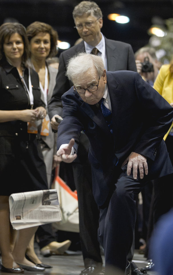 Photo -   Warren Buffett, chairman and CEO of Berkshire Hathaway tosses a newspaper during a newspaper tossing competition in Omaha, Neb., Saturday, May 5, 2012. Bill Gates watches at rear. Berkshire Hathaway is holding it's annual shareholders meeting this weekend. (AP Photo/Nati Harnik)