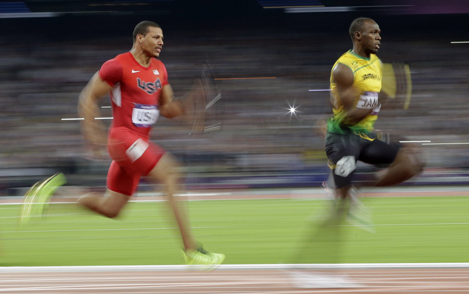 Photo -   Jamaica's Usain Bolt leads USA's Ryan Bailey to win the gold medal in the en's 4x100-meter during the athletics in the Olympic Stadium at the 2012 Summer Olympics, London, Saturday, Aug. 11, 2012. (AP Photo/Matt Slocum)