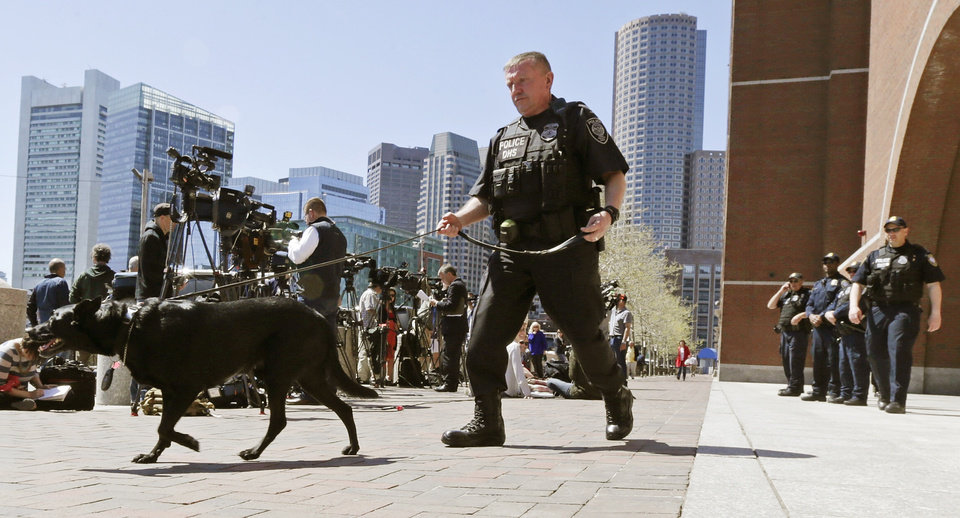 Photo - A Department of Homeland Security police officer patrols with his dog outside the Moakley Federal Courthouse in Boston, Mass., Wednesday, May 1, 2013.  Three suspects were taken into custody in the Boston Marathon bombing case including two college friends of Dzhokhar Tsarneav, according to officials.  (AP Photo/Charles Krupa)