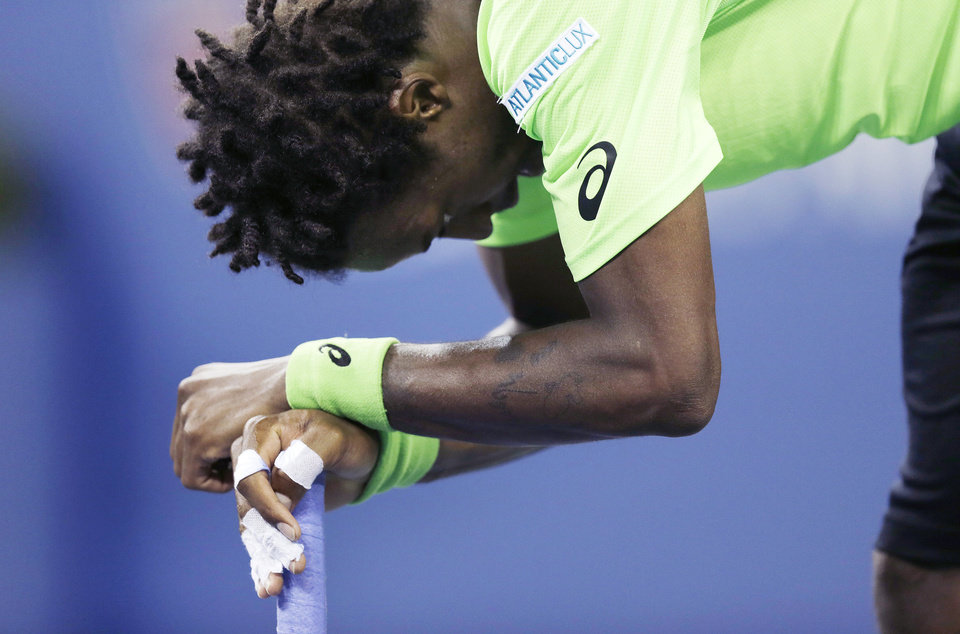 Photo - Gael Monfils, of France, rests on his racket after losing a point during the fifth set against Roger Federer, of Switzerland, during the quarterfinals of the U.S. Open tennis tournament, Thursday, Sept. 4, 2014, in New York. Federer defeated Monfils 4-6, 3-6, 6-4, 7-5, 6-2. (AP Photo/Charles Krupa)