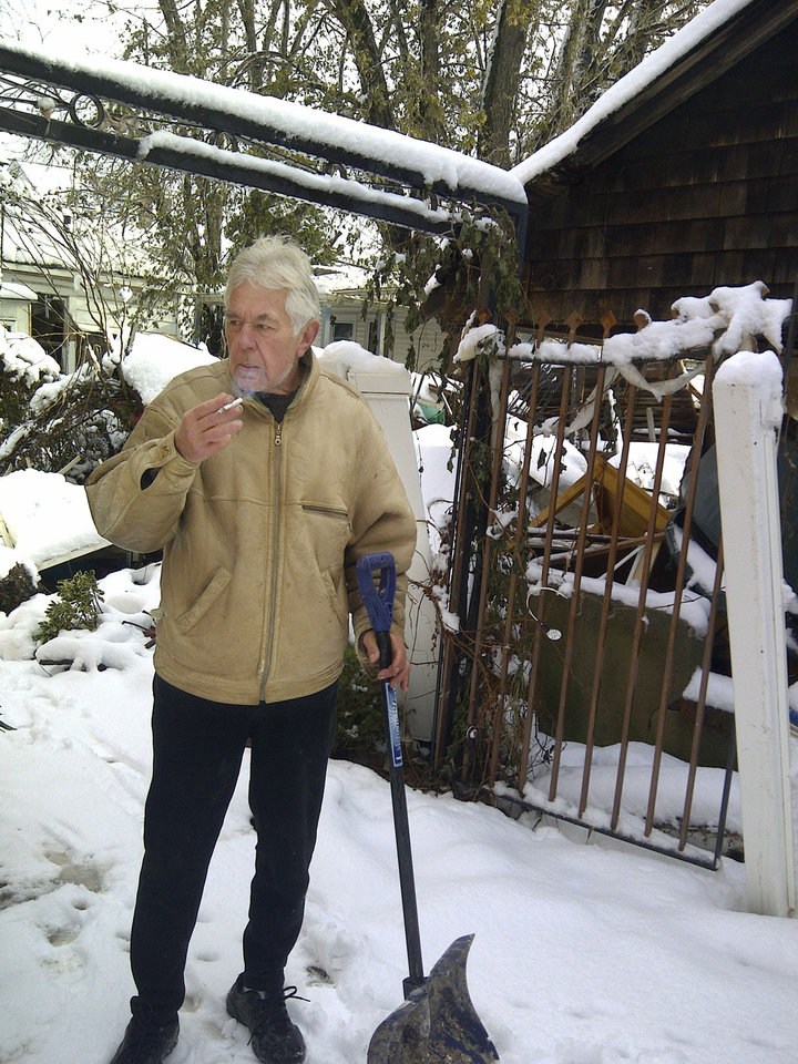 "Vladimir Repnin, 63, emerges from his powerless home with snow shovel in hand and a cigarette, Thursday, Nov. 8, 2012, in New Dorp Beach, in the Staten Island borough of New York. Reflecting his isolation from the outside world he asked; ""Who won? Obama?"" (AP Photo/Tom Hays)"