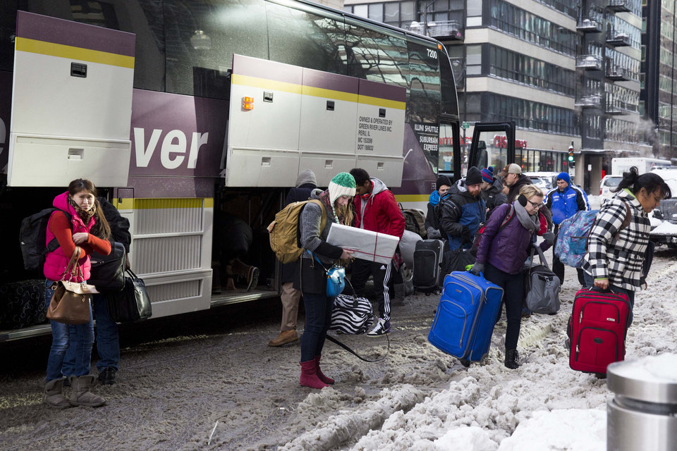 Photo - Passengers arrive at Union Station after their Amtrak train from Los Angeles became stuck in snow drifts on Tuesday, Jan. 7, 2014, in Chicago. The severe weather forced hundreds of Amtrak passengers to spend the night onboard three trains stranded due to the snow in northern Illinois. (AP Photo/Andrew A. Nelles)